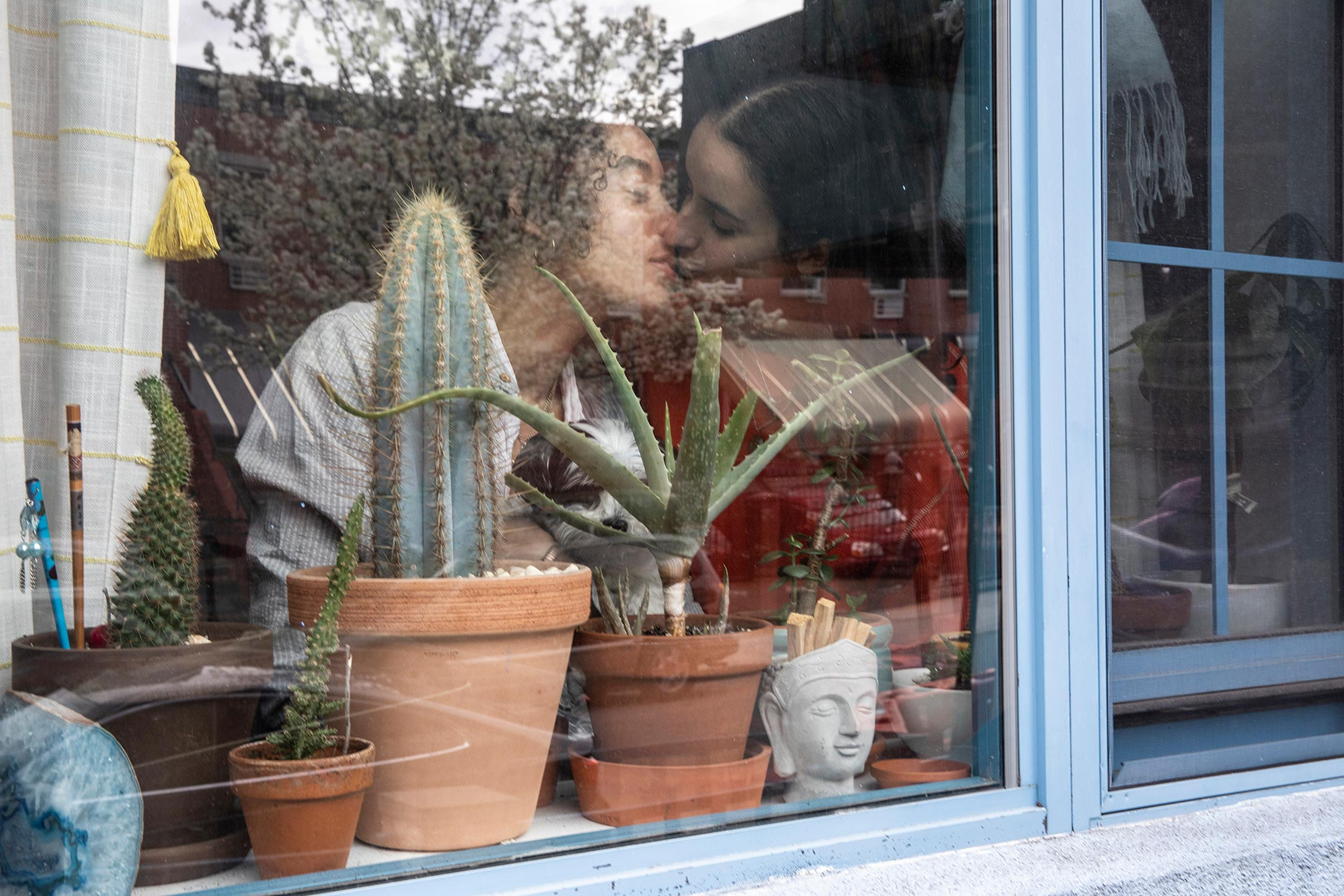 From the outside of the window, a couple are seen kissing.