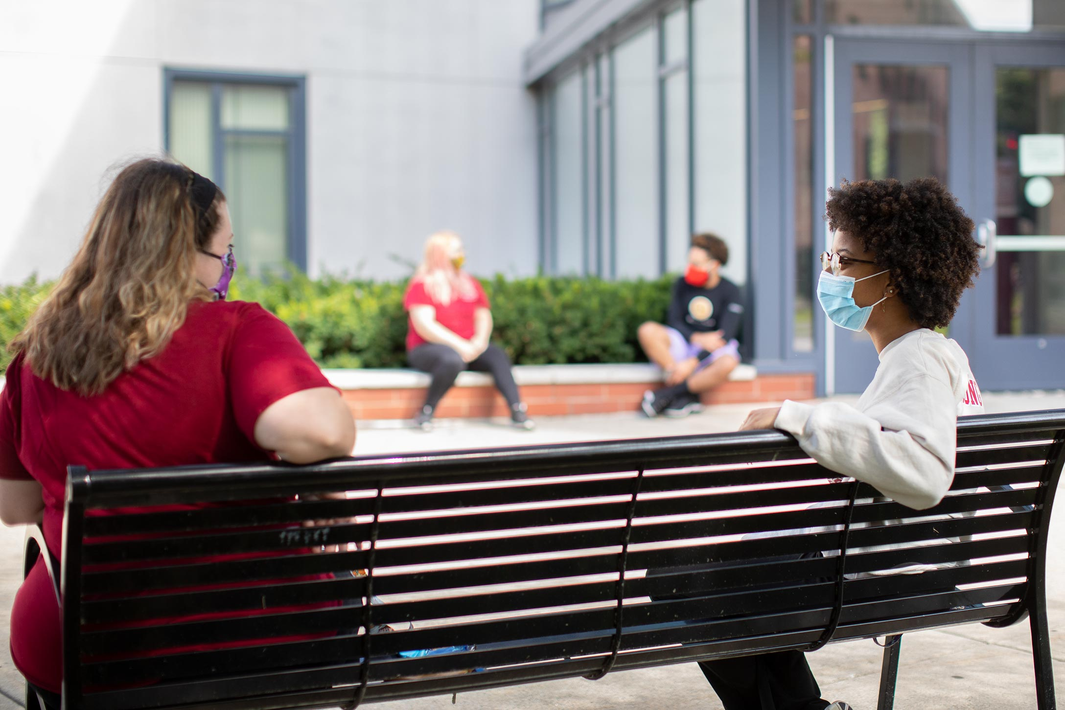 Students wearing face masks are shown conversing from opposite ends of a bench.