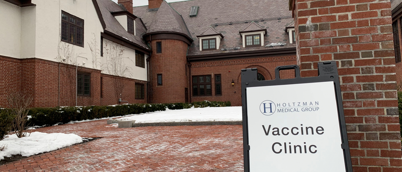 Sign for Holtzman Medical Group vaccine clinic outside Shaw Hall on Mount Ida Campus