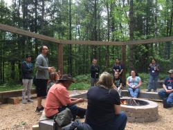 """Kyle Whyte, MSU, speaks about """"Indigenous Planning as a career"""" at the Woodhenge outdoor learning site on the CMN campus in Keshena Wisconsin.  Photo: C. Caldwell"""
