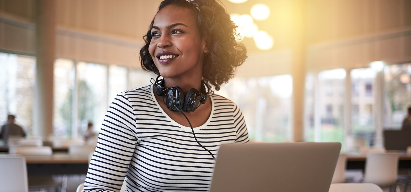 Woman in black and white striped shirt smiling with laptop
