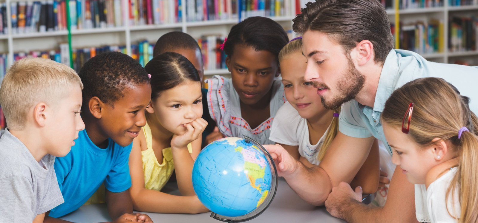 Bearded male teacher and elementary school-age students looking at a globe