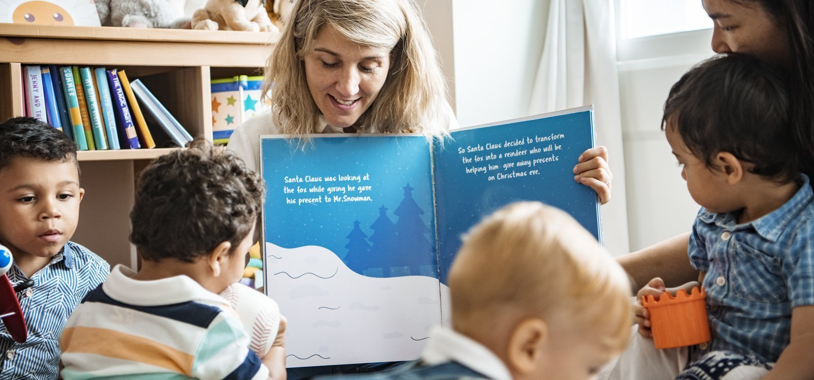 Middle aged pre-school teacher reading to young children.