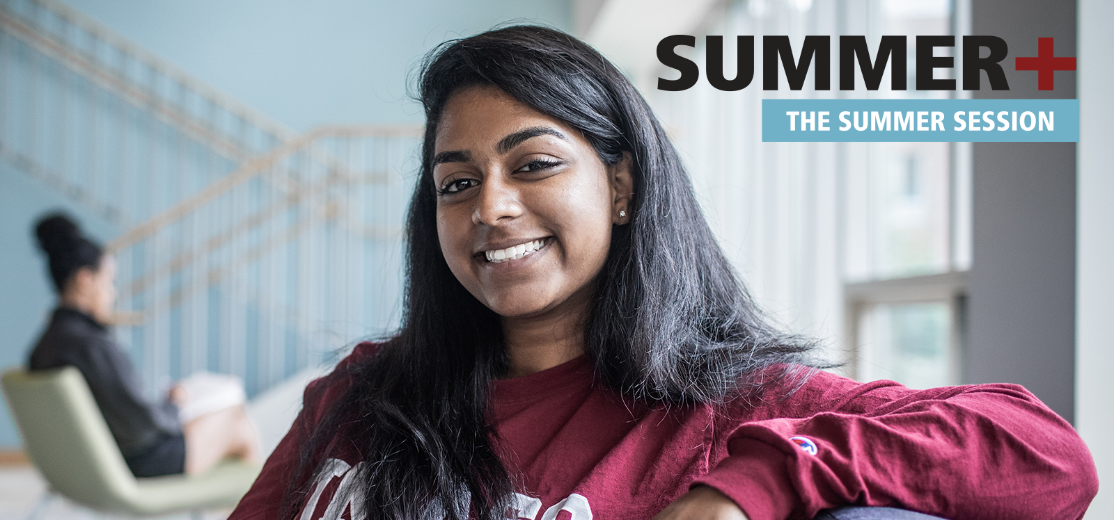 Summer+: the summer session. Smiling female student in UMass Amherst shirt