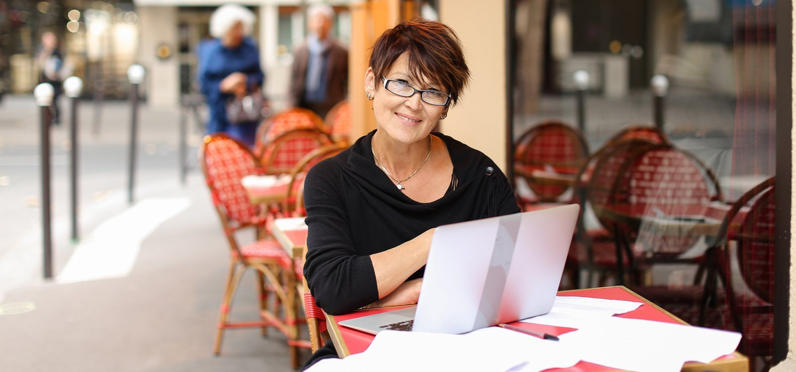 Woman in glasses outside at a café writing on a laptop