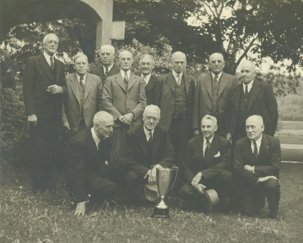 Class of 1892 posing outside at their 50th reunion. Back row: Faneuf, Rogers, Knight, Williams, Lyman, Willard, Field, and Toylor. Front row: Emerson, Boynton, Holland, 1942
