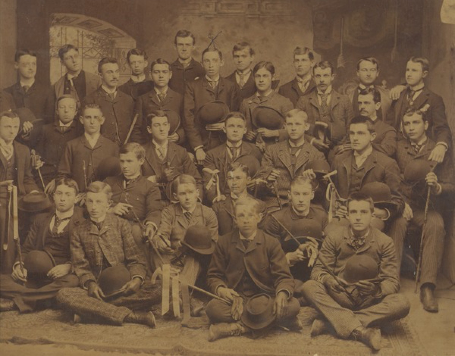 Members of the class of 1890 pose with canes, gloves and bowler hats in front of a backdrop. Fred A. Smith is pictured with an x above his head., ca. 1890