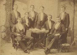 Members of the class of 1890 pose in front of a backdrop, ca. 1890