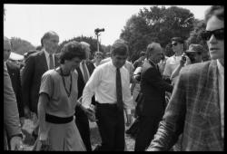 Kitty and Mike Dukakis (hand over face) walking hand-in-hand at the 25th Anniversary of the March on Washington, August 27, 1988