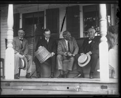 Harvey Firestone, Calvin Coolidge (with sap bucket), Henry Ford, and Thomas Edison (l. to r.) seated on a porch, Grace Coolidge looking on, ca. 1924