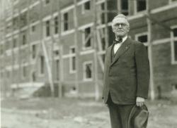 Hugh P. Baker standing in front of building construction, 1946