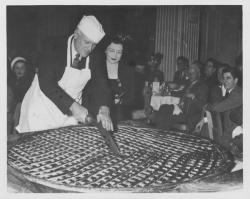 Ralph A. Van Meter cutting an enormous pie, January 1949
