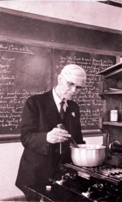 Walter W. Chenoweth stirring a pot on stove, in laboratory, ca. 1941