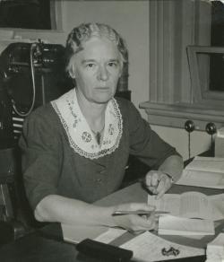 Margaret Hamlin sitting indoors, working at desk, ca. 1935