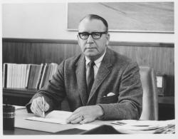 Warren Pierce McGuirk, sitting at desk with pen in hand, ca. 1950