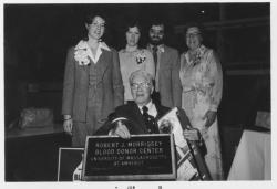 Robert J. Morrissey, seated, holding a plaque and gifts in front of three unidentified women and one man, ca. 1978