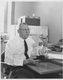 George Robert Richason seated at office desk reviewing a slide, ca. 1967