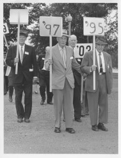 Charles Peters, Albert Parsons, and Ralph Drury holding class signs at 1954 reunion, 1954