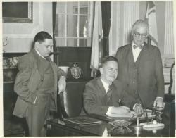 Governor Bradford signing the bill to change the name to University of Massachusetts, Senator Ralph C. Mahar, and President Hugh Potter Baker looking on, 1947