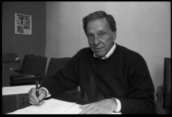 Eugene M. Isenberg: portrait, seated at a desk, May 2, 1995
