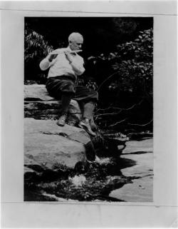 Frank A. Waugh sitting on a rock playing a flute, ca. 1928