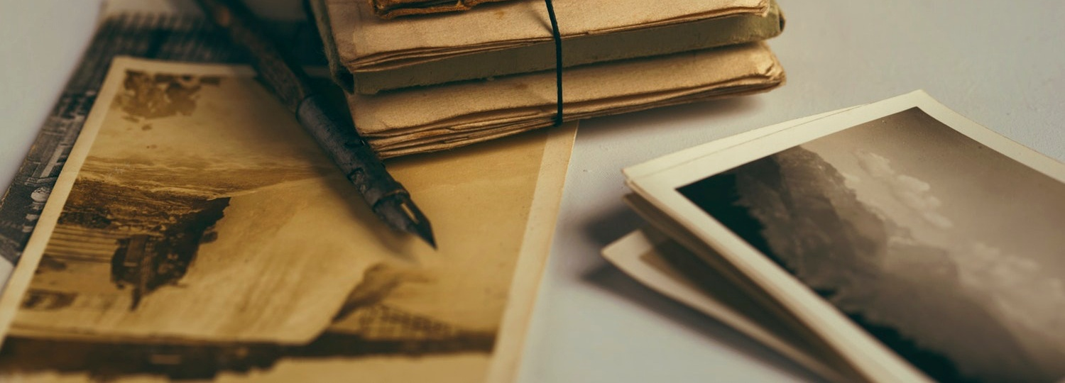 An fountain ink pen sits next to a stack of letters tied with twine and old photographs.
