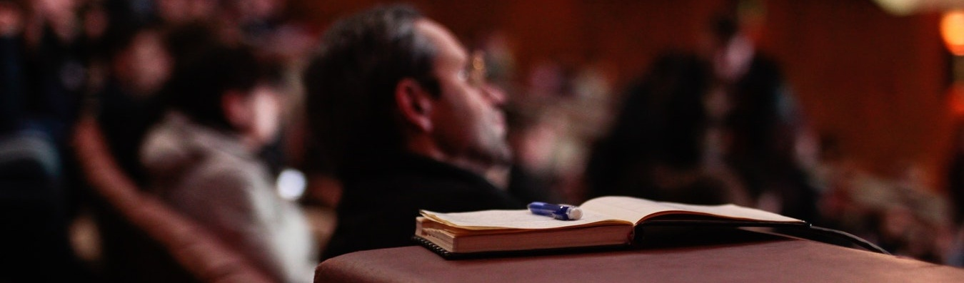 An open book with a pen sits open. In the background, people watch a lecture.