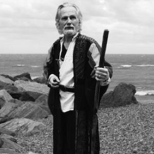 Christ Devine as Prospero on a beach in grayscale