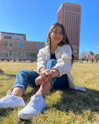 Farah Sabir sits on the University of Massachusetts campus with the tower of the W.E.B. Du Bois Library looming in the background
