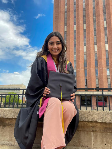 Farah Sabir sits on the University of Massachusetts campus in her graduation robes with the tower of the W.E.B. Du Bois Library looming in the background