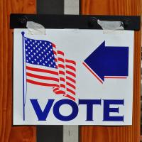 "Sign with the word ""Vote"" and an American flag"