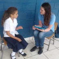 Olivia Laramie talking with a student in Honduras