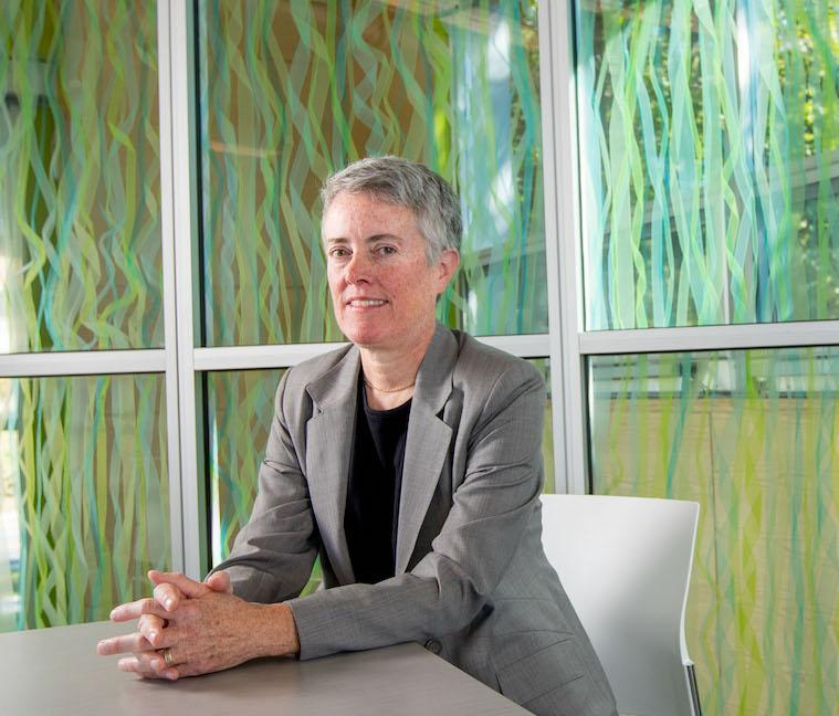 Professor Lee Badgett sitting at a conference table