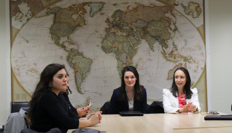 Students sitting at a conference table in front of a world map