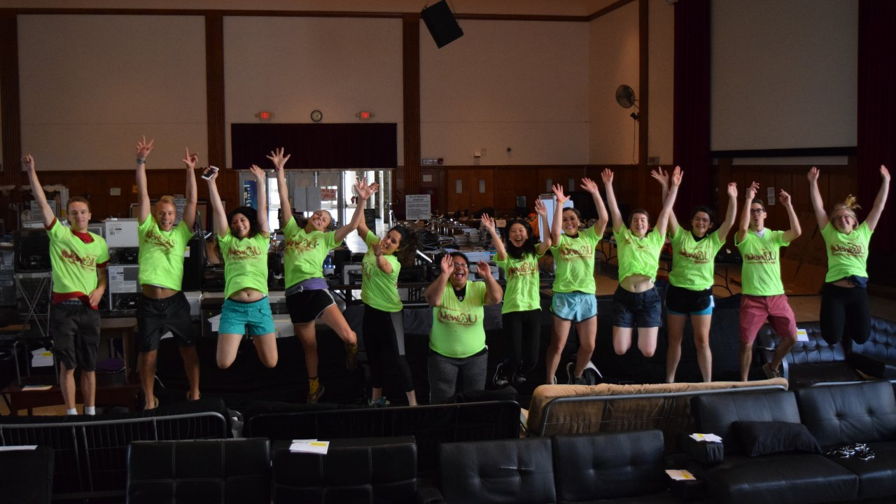 Twelve students volunteering for New2U, all jumping in the air and smiling at the same time!