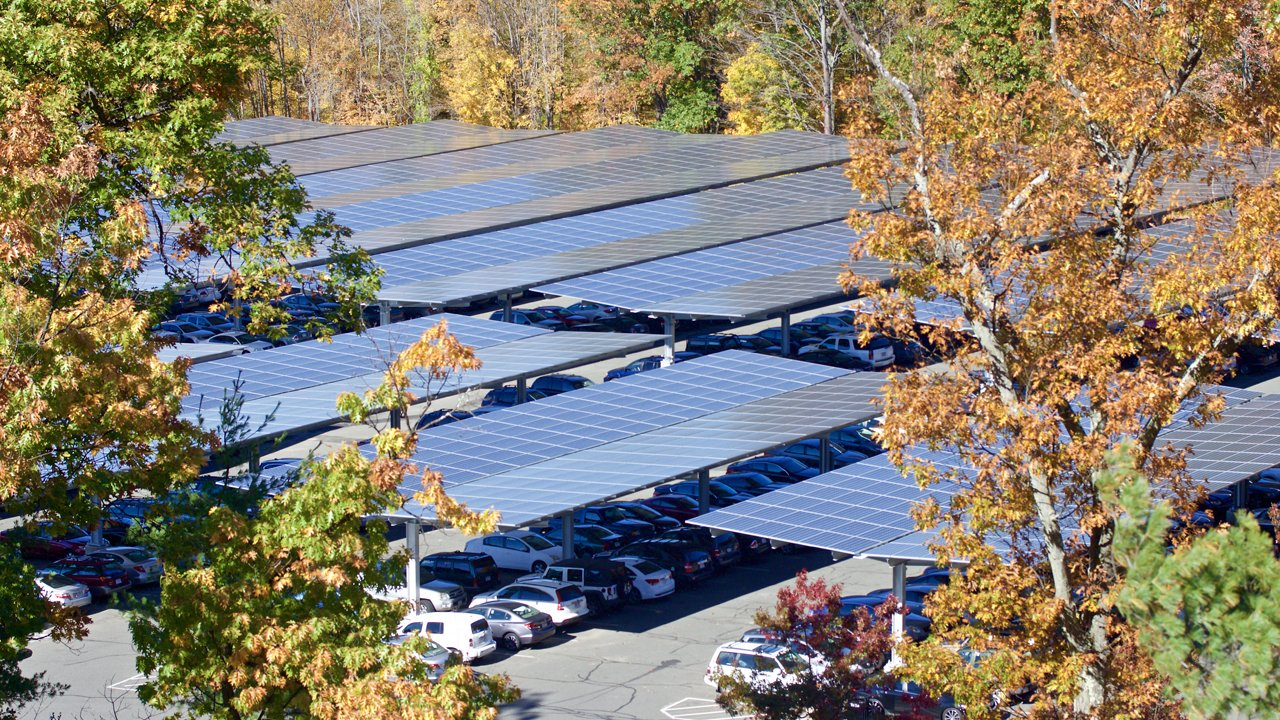 Parking Lot 44 surrounded by fall foliage, with a shot of the solar canopy built above the cars in the parking lot