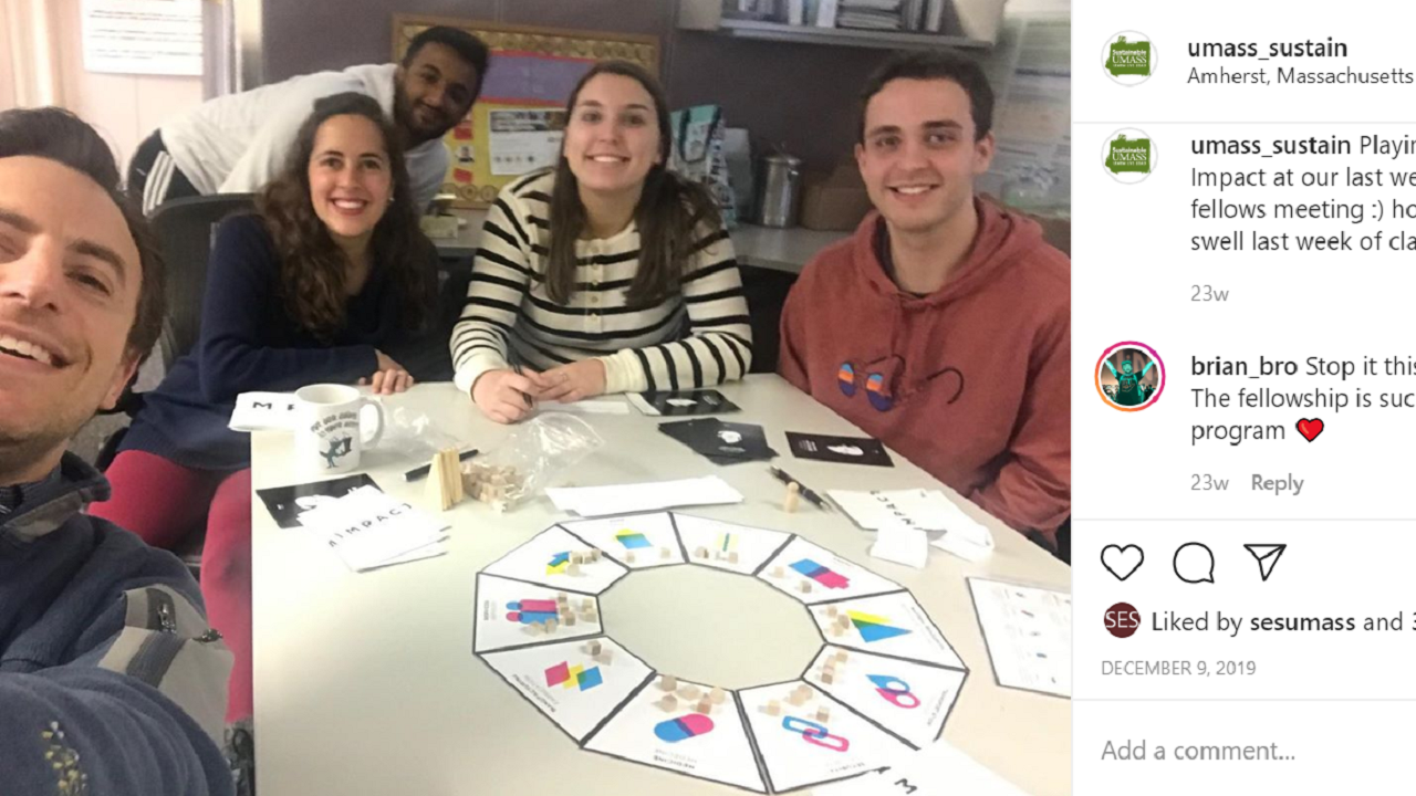 Fellows, the sustainability manager and the sustainability engagement coordinator playing a board game called IMPACT