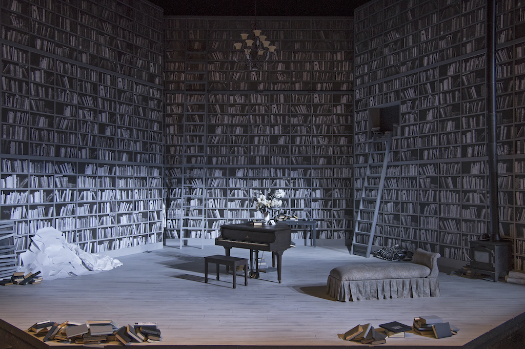 A stage set, filled with books to the ceiling, arranged around a piano