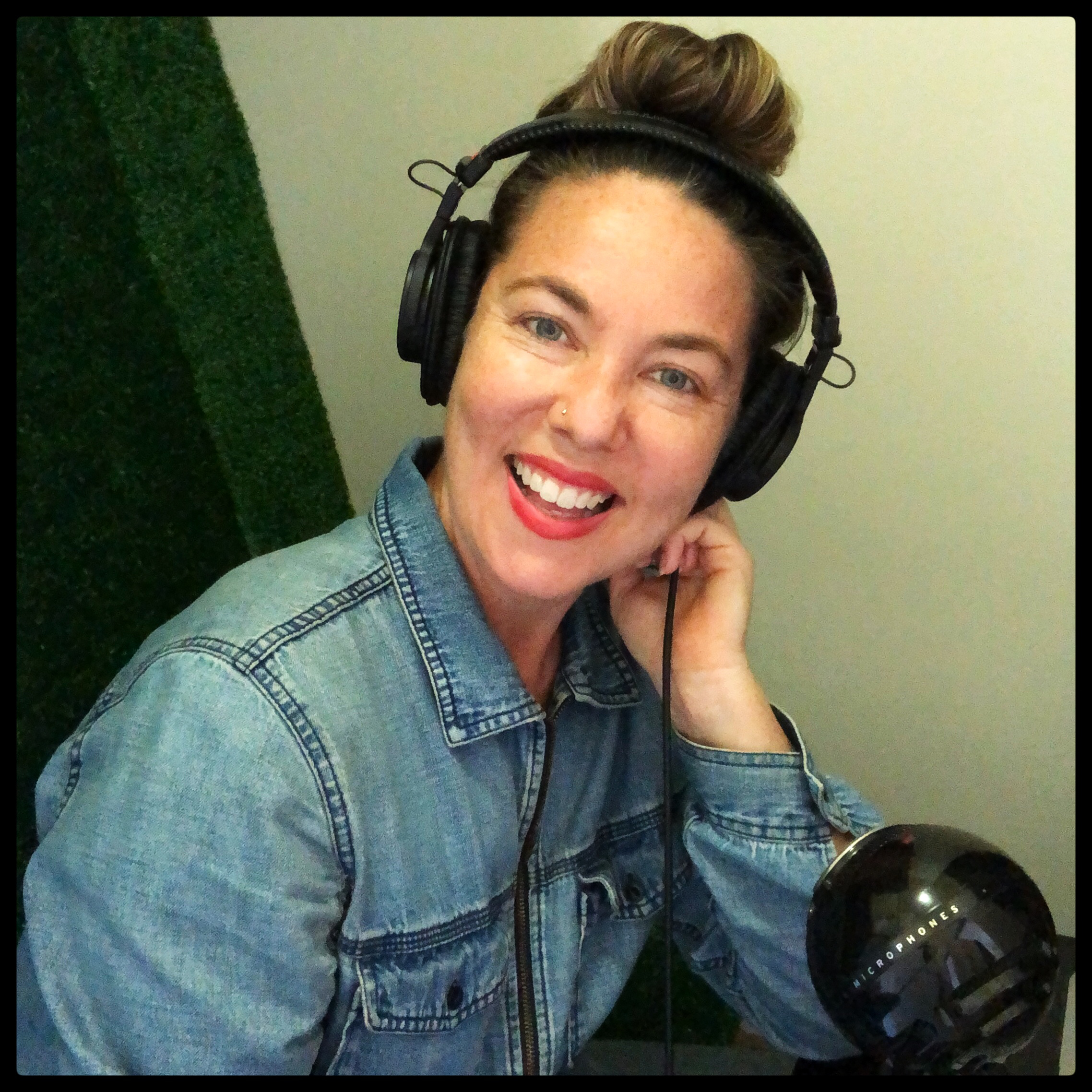 A white woman in her thirties with blue eyes, dark brown hair piled on her head in a messy bun. She is wearing large headphones and smiling