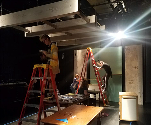 Students work to install theatrical equipment in a small theater space