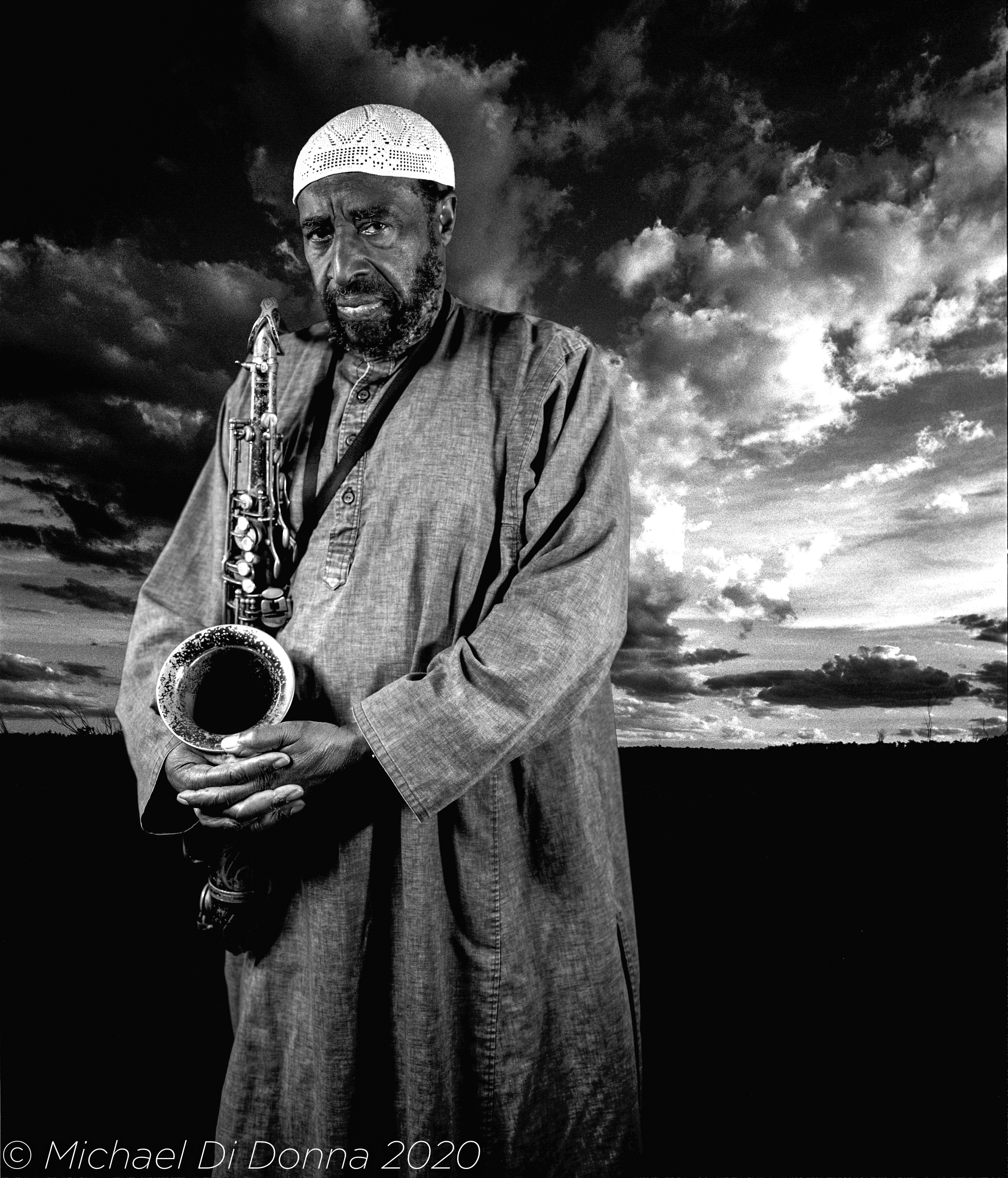 Dr Yusef Lateef, photographed in front of a cloudscape, holding his instrument