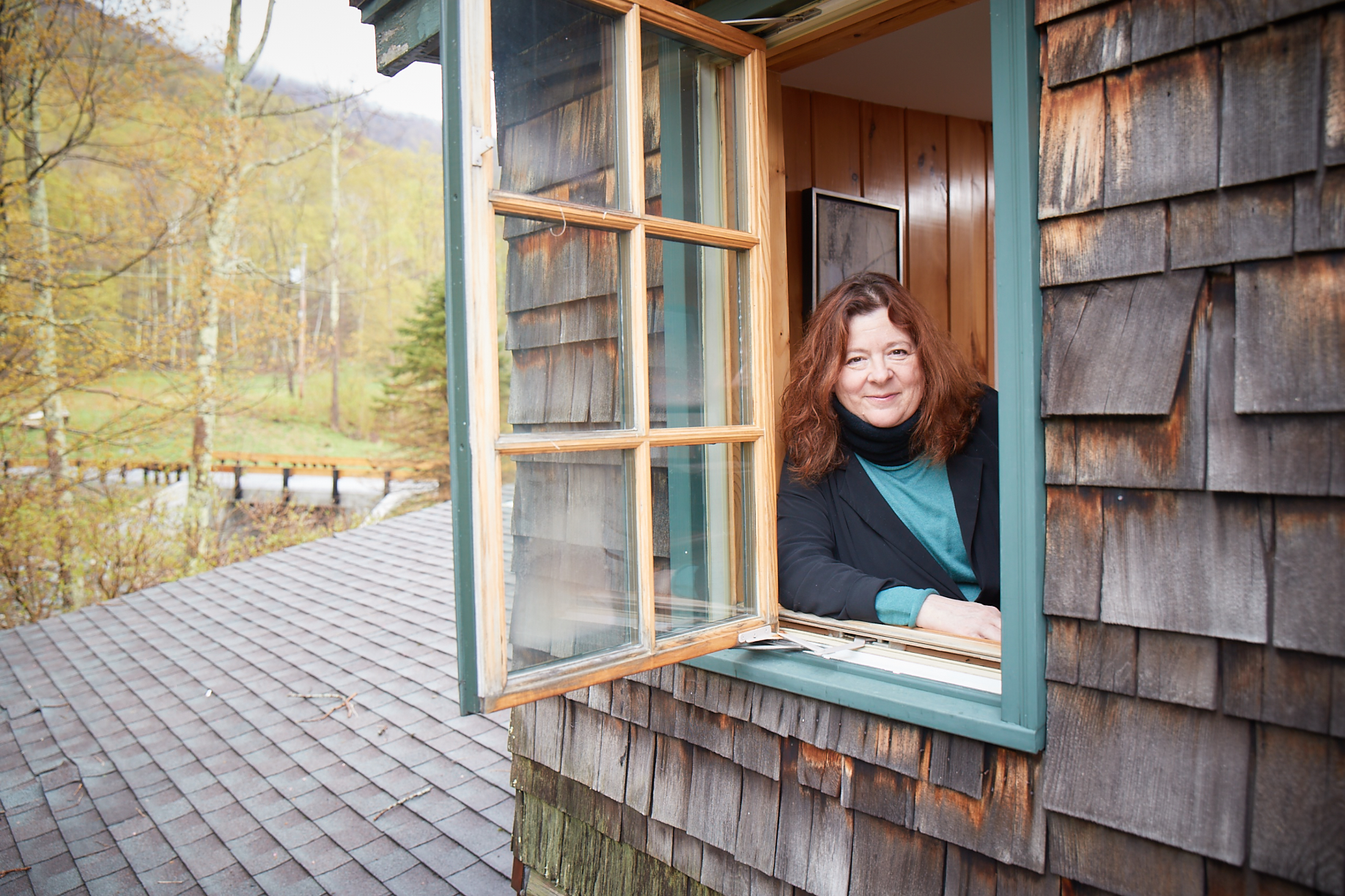 Photo of playwright Theresa Rebeck leaning out a window