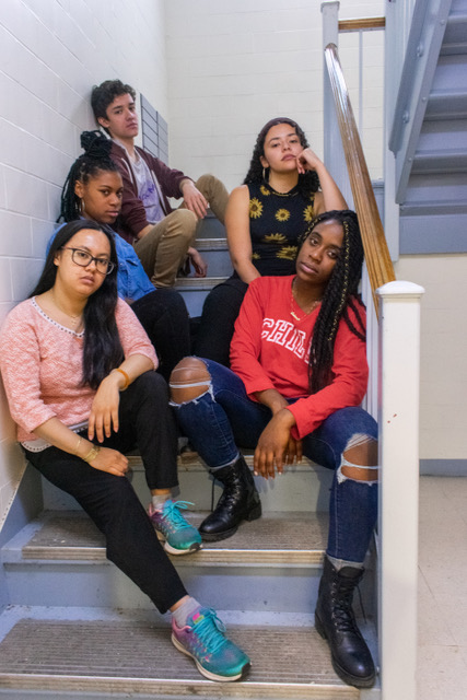 group shot of five college students sitting in a stairwell