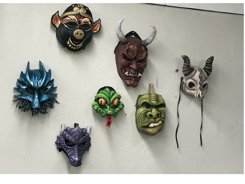 A display of a variety of masks in vivid colors, depicting fantastical creatures or people, created by students