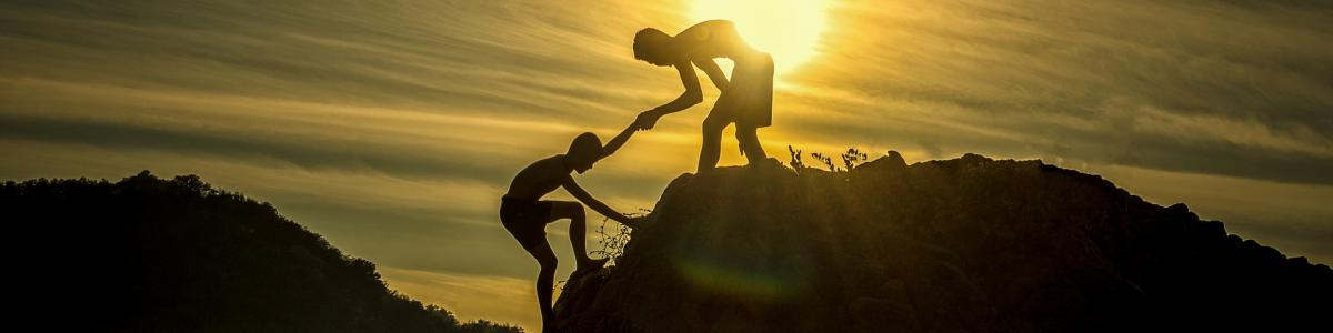 Photo illustration of one person helping another up a hill