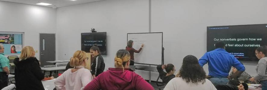 Students standing in a classroom while an instructor writes on a whiteboard.