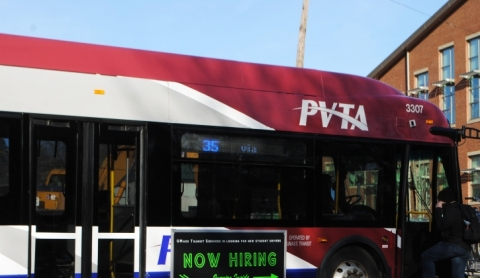 "Passenger boards a bus that has a ""now hiring"" display on the side"