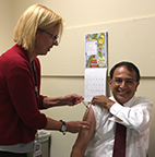 UHS nurse Ann Becker gives Chancellor Subbaswammy a flu shot