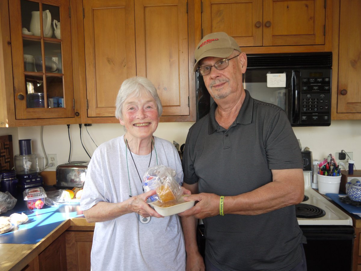 Volunteer Meals on Wheels driver Alan Coutinho (right) delivers a hot meal to Joan Wilson at her home in Shelburne.