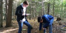 Two students doing field research in a forest clearing